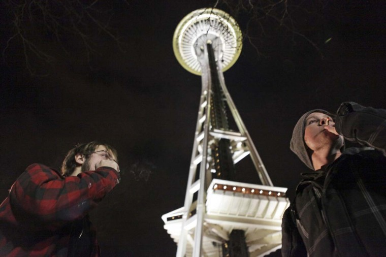 People light up near the Space Needle after the law legalizing the recreational use of marijuana went into effect in Seattle, Washington. With Washington state the first in the nation legalizing marijuana possession for adult recreational use, Seattle's city attorney issued a stern warning on Wednesday to those waiting to celebrate - no pot puffing in public. (Cliff Despeaux/Reuters photo)