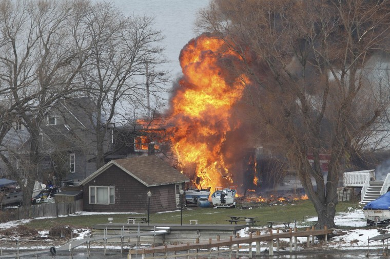 A house burns after a man set fire and then shot and killed a responding police officer and a firefighter while injuring two other firefighters in Webster, New York, December 24, 2012. A gunman shot dead two volunteer firefighters and injured two others when he ambushed them at the scene of an early morning house fire in a suburb of Rochester, New York, authorities said on Monday. (Jamie Germano/Democrat and Chronicle/Reuters)