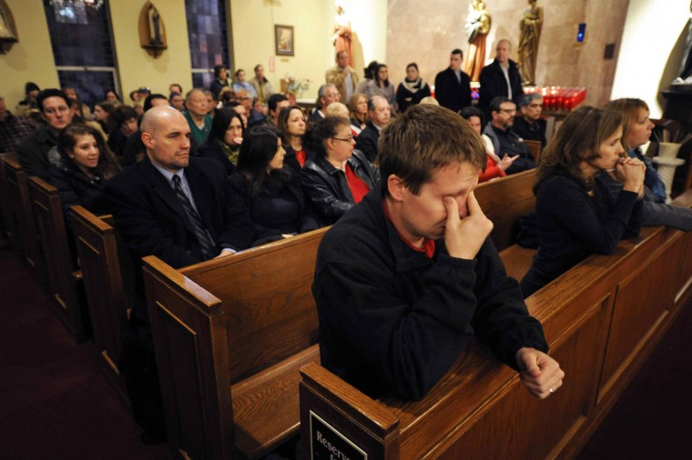 Mourners gather inside the St. Rose of Lima Roman Catholic Church at a vigil service for victims of the Sandy Hook Elementary School shooting that left at least 27 people dead - many of them young children - in Newtown, Connecticut. (Andrew Gombert/Pool)