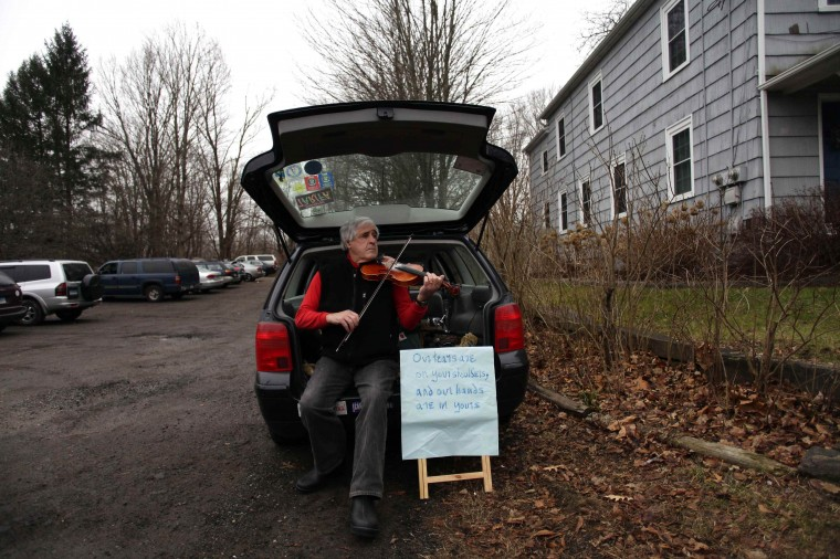 A man plays a violin along Church Hill Road in Newtown, Connecticut December 16, 2012. Twelve girls, eight boys and six adult women were killed in a shooting on Friday at the Sandy Hook Elementary School in Newtown. (Joshua Lott/Reuters)