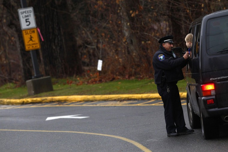Easton police officer J. Sollazzo talks to a child coming to school in Newtown, Connecticut. The schools of Newtown, which stood empty in the wake of a shooting rampage that took 26 of their own, will again ring with the sounds of students and teachers on Tuesday as the bucolic Connecticut town struggles to return to normal. (Eric Thayer/Reuters)