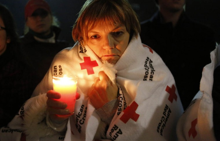 A woman wrapped in a Red Cross blanket holds a candle outside Newtown High School where U.S. President Barack Obama was speaking at a vigil for families of victims of the Sandy Hook Elementary School shooting in Newtown, Connecticut December 16, 2012. Obama on Sunday consoled the Connecticut town shattered by the massacre of 20 young schoolchildren, lauding residents' courage in the face of tragedy and saying the United States was not doing enough to protect its children. (Kevin Lamarque/Reuters)