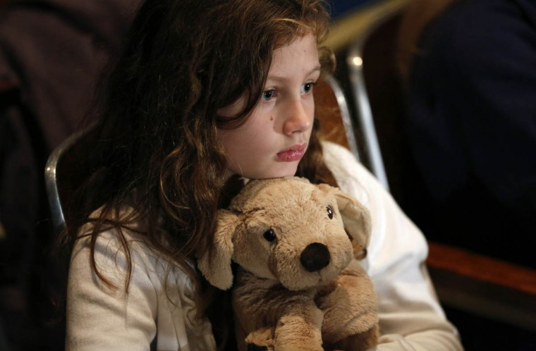 A girl holds a stuffed animal given to her by the Red Cross during a vigil held at Newtown High School for families of victims of the Sandy Hook Elementary School shooting in Newtown, Connecticut December 16, 2012. (Kevin Lamarque/Reuters)