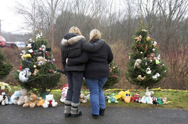 Two women pay their respects for the victims of the shooting at a memorial near Sandy Hook Elementary School in Newtown, Connecticut, December 16, 2012. Worshippers filled Sunday services to mourn the victims of a gunman's elementary school rampage that killed 20 children and six adults with President Barack Obama due to appear later at an interfaith vigil to help this shattered Connecticut town recover. (Michelle McLoughlin/Reuters)