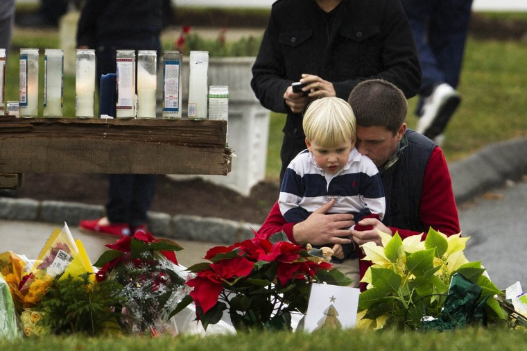 A man embraces a young boy as they look at a memorial in front of the St. Rose of Lima Catholic church in Newtown, Connecticut December 16, 2012. Worshipers filled Sunday services to mourn the victims of a gunman's rampage at Sandy Hook elementary school in Newtown that killed 20 children and six adults with President Barack Obama due to appear later at an interfaith vigil to help this shattered Connecticut town recover. (Lucas Jackson/Reuters)