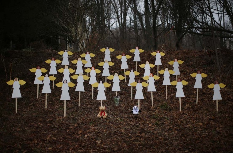 Twenty-seven wooden angel figures are seen placed in a wooded area beside a road near the Sandy Hook Elementary School for the victims of a school shooting in Newtown, Connecticut December 16, 2012. Twelve girls, eight boys and six adult women were killed in the shooting on Friday at the Sandy Hook Elementary School in Newtown. (Mike Segar/Reuters)