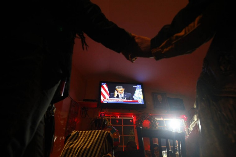 People hold hands in a bar near Sandy Hook Elementary School as U.S. President Barack Obama speaks in Newtown, Connecticut, December 16, 2012. Obama on Sunday consoled the Connecticut town shattered by the massacre of 20 young schoolchildren, lauding residents' courage in the face of tragedy and saying the United States was not doing enough to protect its children. (Eric Thayer/Reuters)