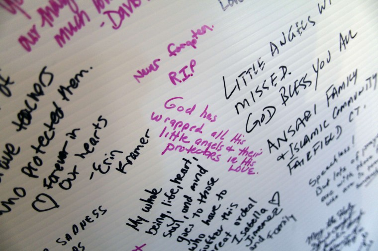 Messages are written on a board dedicated to the victims of the Sandy Hook Elementary School shooting, displayed at Saint Rose of Lima Roman Catholic Church in Newtown, Connecticut. December 15, 2012. People in the small Connecticut community were still grieving a day after one of the deadliest mass shootings in U.S. history. (Eric Thayer/Reuters)