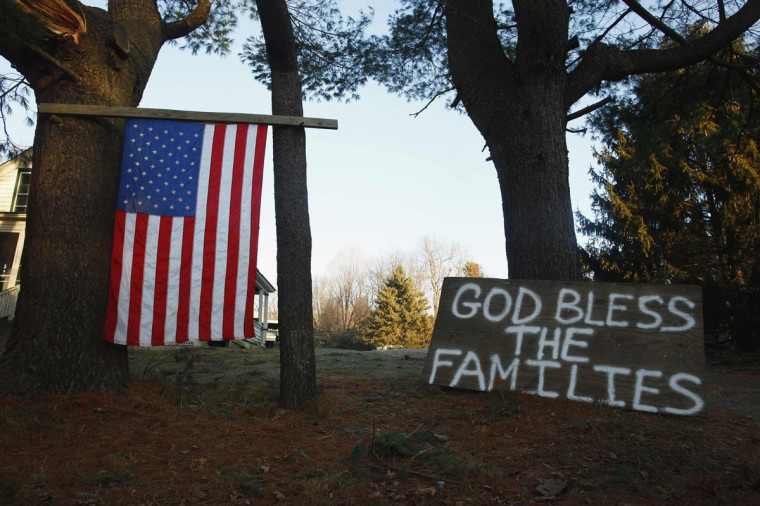 A sign and a U.S. national flag are seen near Sandy Hook Elementary School in Sandy Hook in Newtown, Conn. Residents of the small community of Newtown were reeling a day after one of the deadliest mass shootings in U.S. history. (Eric Thayer/Reuters)