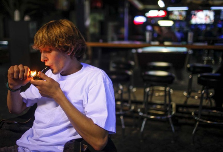 Russell Diercks smokes marijuana inside of Frankie Sports Bar and Grill in Olympia, Washington on December 9, 2012. (Nick Adams/Reuters)