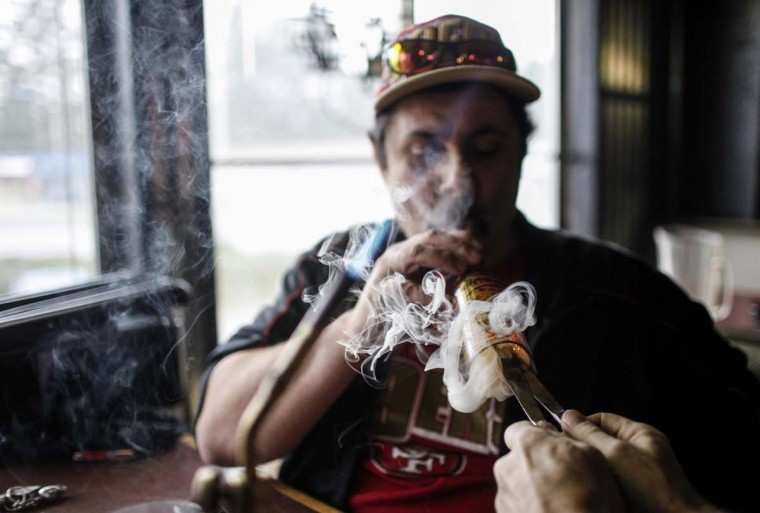 Medical marijuana patient Robert Badillo smokes marijuana oil inside Frankie Sports Bar and Grill in Olympia, Washington December 9, 2012. (Nick Adams/Reuters)