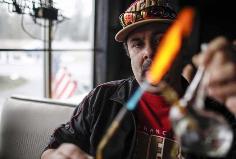 Medical marijuana patient Robert Badillo heats up a pipe to smoke marijuana oil inside Frankie Sports Bar and Grill in Olympia, Washington December 9, 2012. (Nick Adams/Reuters)