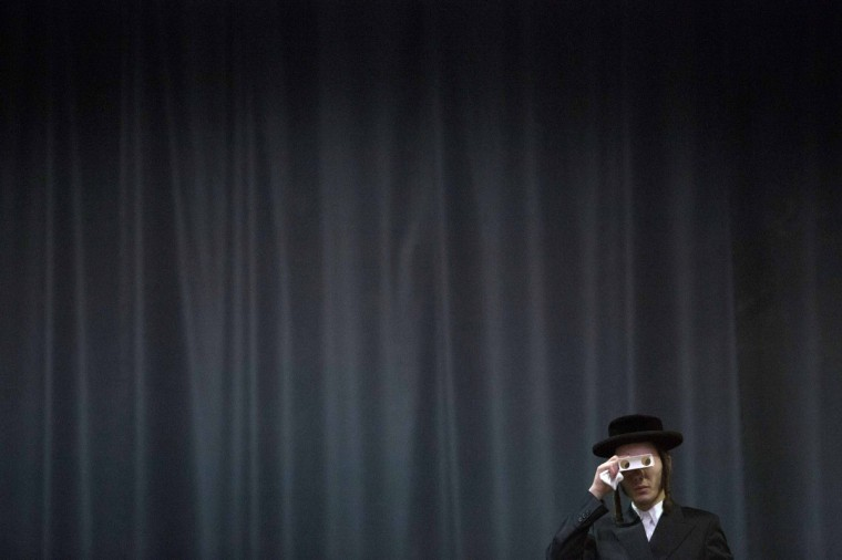 A man looks through a pair of disposable binoculars during a gathering for Satmar Hasidic Jews in New York. Thousands attended to celebrate the 68th anniversary of the rescue of their founder, Rabbi Joel Teitelbaum, from the clutches of the Nazis at the mass gathering. (Andrew Kelly/Reuters)