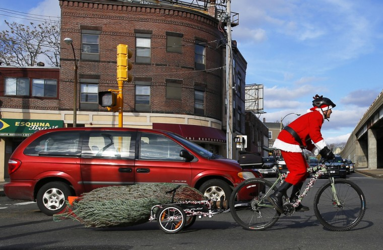 Jimmy Rider delivers an eight-foot tall Christmas tree on a trailer attached to his bicycle, as part of his Ever-Green Delivery service, in Somerville, Massachusetts. (Brian Snyder/Reuters)