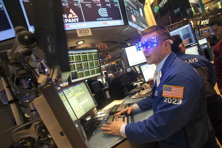 "Trader Joseph Mastrolia wears ""2013"" glasses celebrating New Year's Eve as he works on the floor of the New York Stock Exchange in New York, December 31, 2012. (Keith Bedford/Reuters)"