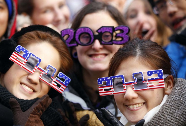 Akane Okamoto (L) and Kurara Hayashi (R) of Osaka, Japan pose with Allison Hoff of North Dakota as New Year's revellers begin to fill up Times Square in New York, December 31, 2012. (Gary Hershor/Reuters)