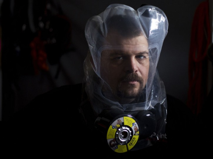 "Phil Burns demonstrates the air purifying SCape Mask at his home in American Fork, Utah, on December 14, 2012. Burns is part of the ""prepper"" movement, a group of people actively preparing for emergencies. While most preppers discount the Mayan calendar doomsday prophecy, many are still getting ready for potential catastrophes as the end of the year approaches. (Jim Urquhart/Reuters)"