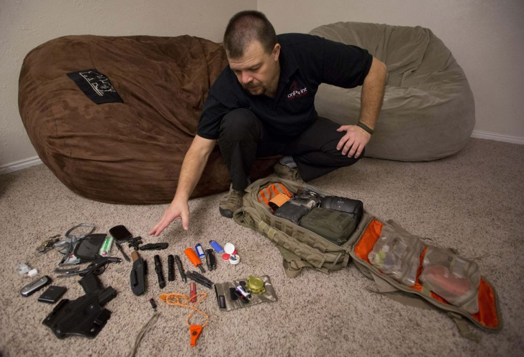 "Phil Burns inventories some of the gear in a backpack full of survival supplies at his home in American Fork, Utah, on December 14, 2012. Burns is part of the ""prepper"" movement, a group of people actively preparing for emergencies. While most preppers discount the Mayan calendar doomsday prophecy, many are still getting ready for potential catastrophes as the end of the year approaches. (Jim Urquhart/Reuters)"