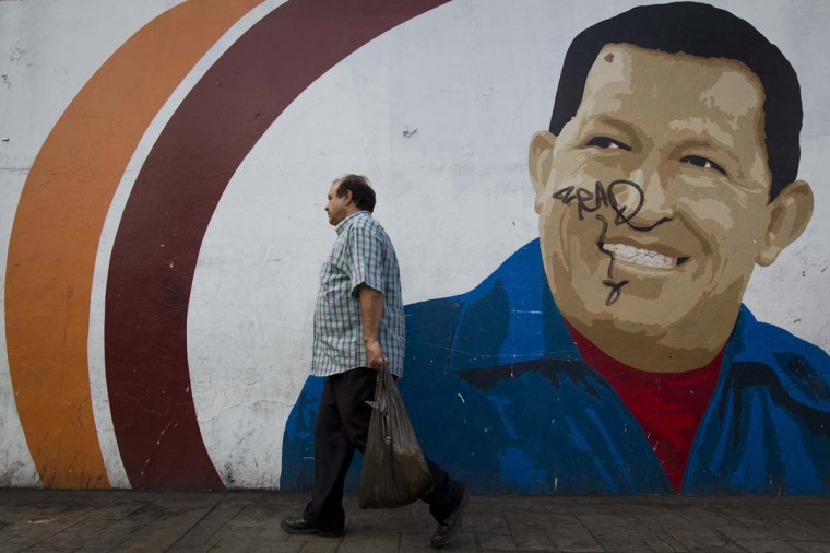 "A man walks past a mural depicting Venezuelan President Hugo Chavez in Caracas December 31, 2012. Chavez has suffered more complications following complex cancer surgery in Cuba and remains in a ""delicate"" condition, the vice president said on Sunday. (Carlos Garcia Rawlins/Reuters)"