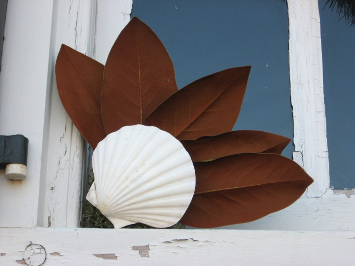 The back side of magnolia leaves and seashells highlight the corner of a window. (Susan Reimer/Baltimore Sun)