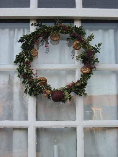 Sometimes simplest is best design. Boxwood, dried fruit slices and a pomegranate are used for this wreath. (Susan Reimer/Baltimore Sun)