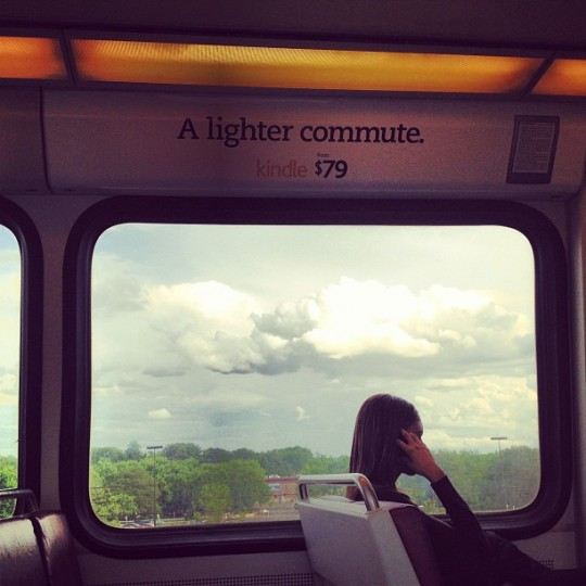 "Underneath an ""A lighter commute"" ad for a Kindle e-reader, a female train passenger is silhouetted against the car's window, which reveals a bright green treeline and light fixtures under large, puffy clouds."