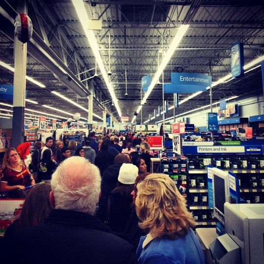 Shoulder-to-shoulder crowd packs Walmart computer section near the printers and ink