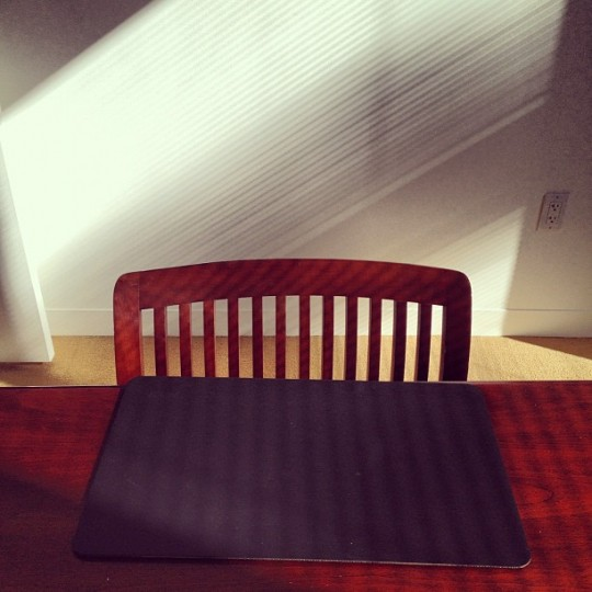 Black placemat set on dark wood table in front of dark wood chair. Filtered natural light and shadows on the white wall behind.