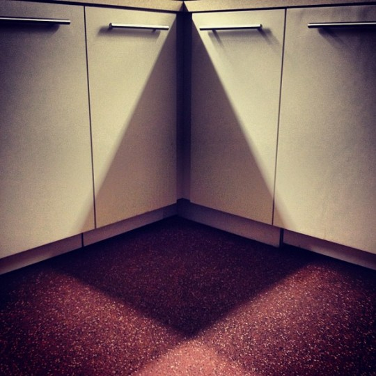 Low angle shot of shadow made at corner of white kitchen cabinets with long horizontal metal handles.