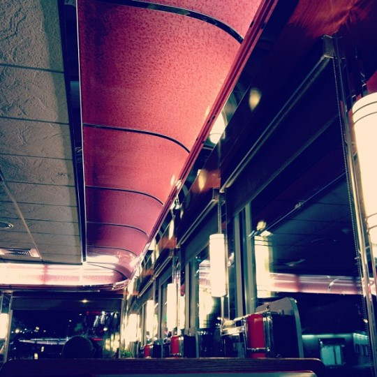 Booth-level view looking up at diner windows reflecting booth's lights and white-paneled ceiling and dark red awning.
