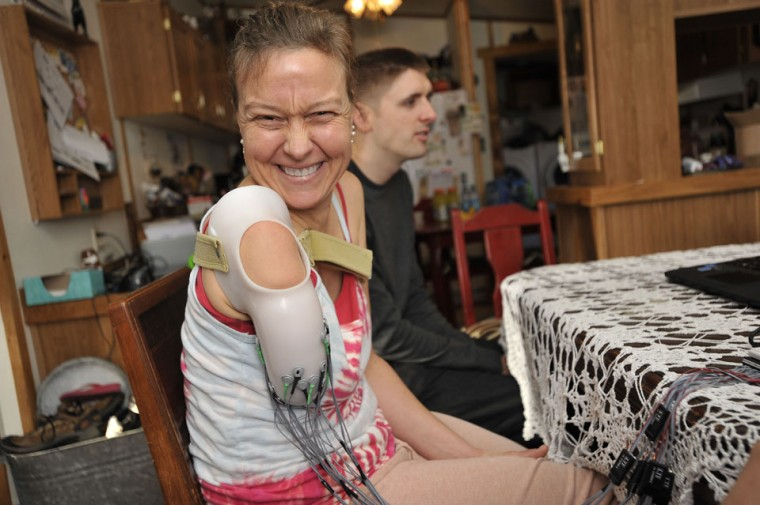 Dec. 16: Medical breakthrough: Dana Burke, a Pennsylvania woman who was shot in the arm 14 years ago, smiles before beginning another day of testing of a thought-controlled prosthetic arm. Mike Powell, a graduate student at Johns Hopkins is sitting next to her. (Kim Hairston/Baltimore Sun)