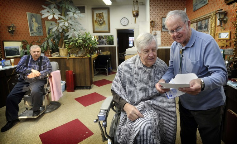 Regular customer Peter Terry of Baltimore, who has been coming to Gennuso's Barbershop on York Road for at least 30 years, looks at photos with barber Charlie Mannin, 81, right, who has worked in this shop for around 50 years. Barber Joseph Lewis, with 50 years experience, is on left. (Barbara Haddock Taylor/Baltimore Sun)