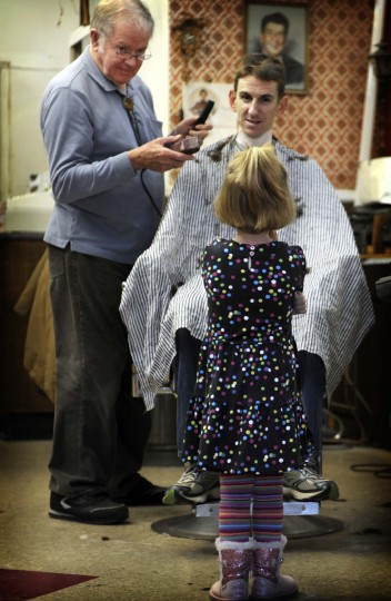 Four year old Gayle Lancaster talks with her dad, Jim Lancaster, as he gets a hair cut from barber Charlie Monnin at Gennuso's Barbershop(Barbara Haddock Taylor/Baltimore Sun)