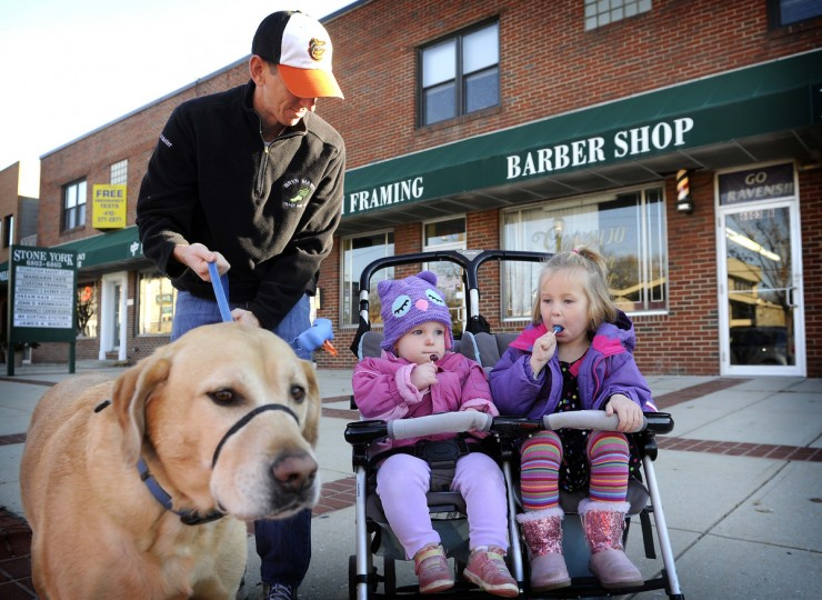 Jim Lancaster leaves Gennuso's Barbershop after a haircut as his daughters, Eleanor, 1, left, and Gayle, 4, eat their lollipops. (Barbara Haddock Taylor/Baltimore Sun)