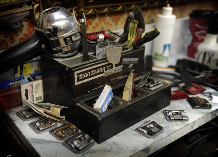 The work station of Charlie Monnin, 81, who has been a barber for over 50 years in Gennuso's Barbershop on York Road, is full of various items he uses on the job. (Barbara Haddock Taylor/Baltimore Sun)