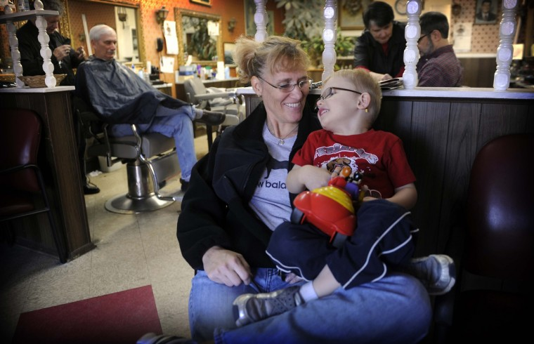 Kim Whittle and her four year old son Andy McCabe wait their turn at Gennuso's Barbershop. (Barbara Haddock Taylor/Baltimore Sun)