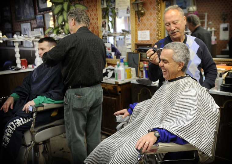 Barber Chuck Gennuso gets a laugh out of customer Henry Kass of Towson as he gets a haircut. The shop has been owned by Chuck Gennuso since 1975. Five barbers work in the shop, with a combined experience level of 250 years cutting hair. On left, Garry Oster cuts Tom Powell's hair. (Barbara Haddock Taylor /Baltimore Sun)
