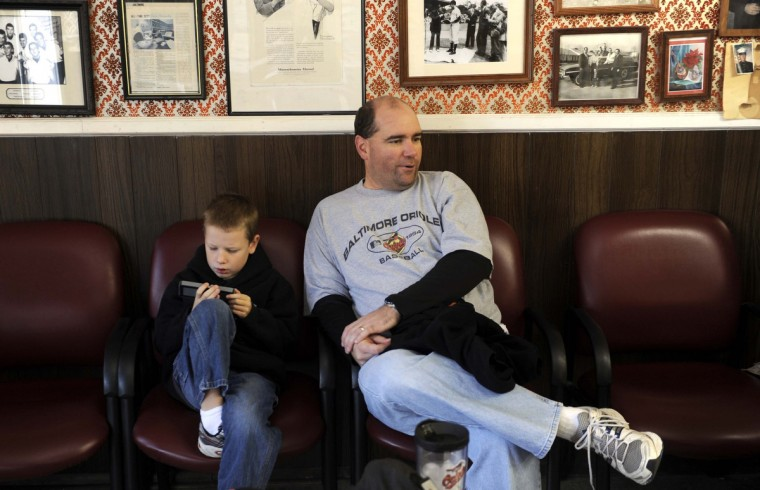 Brendan Karwacki, 6, left, and his dad Kevin wait their turn to see barber Garry Oster. Mr. Oster, who has been cutting hair for 49 years, has cut hair for three generations of the Karwacki family. (Barbara Haddock Taylor/Baltimore Sun)