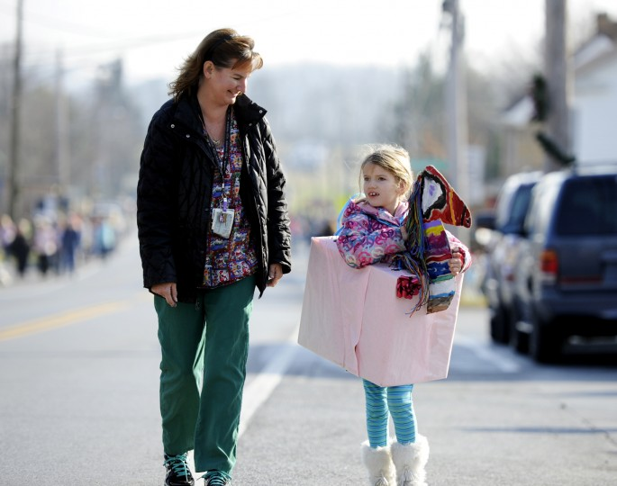 Margaret Small, 6, of Lisbon, walks on Frederick Road with her mom, Mary Small, while wearing a cardboard horse costume at the parade Saturday. (Jon Sham/BSMG)