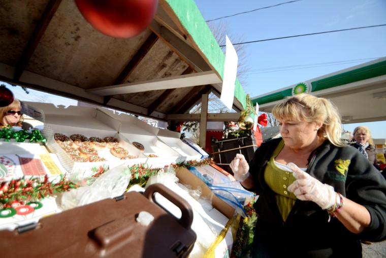 "The Lisbon Town Grill brought Christmas-themed, horse-drawn ""food truck"" to the parade on Saturday, selling doughnuts, coffee and other items. Renee Nehrich takes a request as the stand parks in a gas station lot. (Jon Sham/BSMG)"