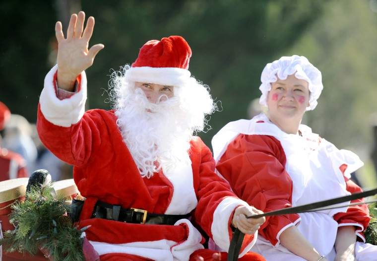 """Santa"" and ""Mrs. Claus"" wave to the crowd during the Lisbon Ole Fashion Christmas Horse Parade. (Jon Sham/BSMG)"