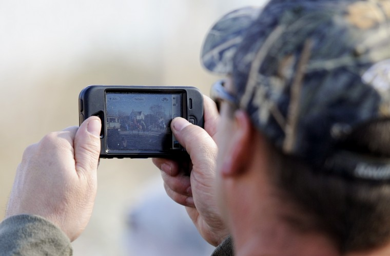 A man snaps a photo of the Lisbon Ole Fashion Christmas Horse Parade on his phone. (Jon Sham/BSMG)