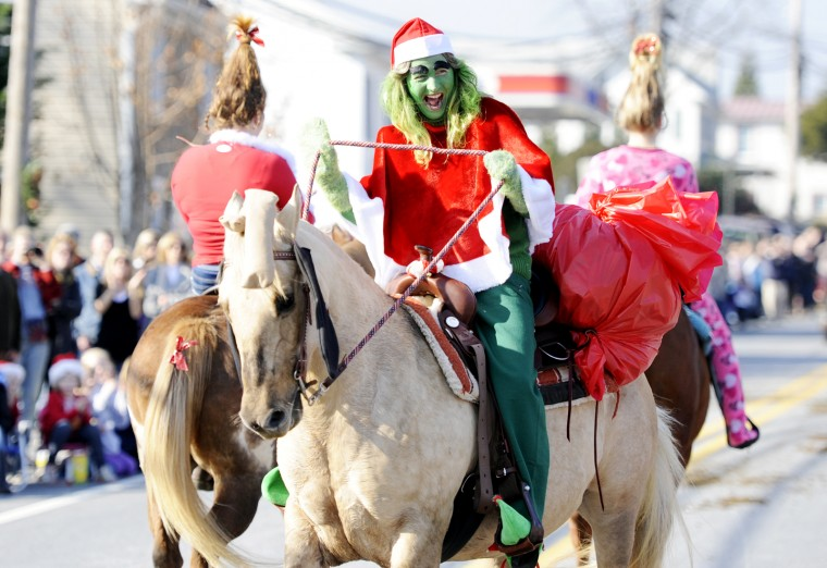 Irene Savage, of Mount Airy, dressed as The Grinch, laughs as she gets turned around on her horse and ends up walking backward for a few steps in the parade. (Jon Sham/BSMG)
