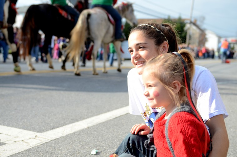McKenzie Ridgely, 16, and her little sister Addison, 3, both of Libertytown watch the parade go by. (Jon Sham/BSMG)