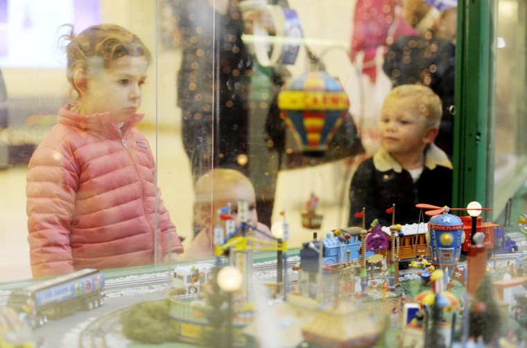 From left, sisters Jane Hughes, 3 and Molly Hughes, 1, of Baltimore, and Griffin Weber, 2, of White Hall stare at the train garden at The Shops at Kenilworth on Friday, Nov. 30, 2012. (Jon Sham/BSMG)