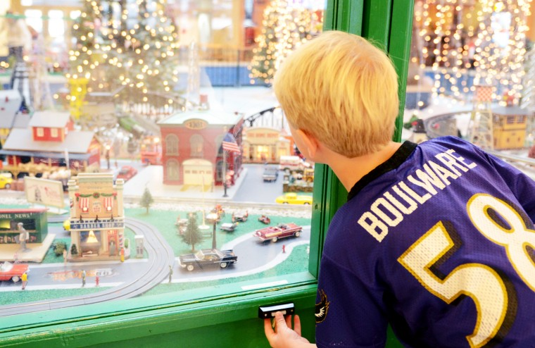 Chase Wise, 6, who used to live in Baltimore but is now visiting from Vermont, presses one of the many buttons at the train garden to activate a moving piece. (Jon Sham/BSMG)