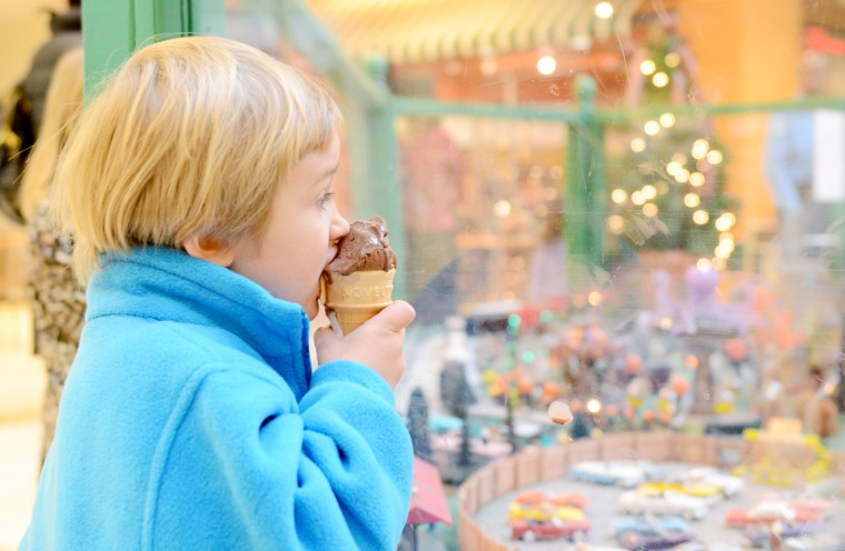 Sawyer Meyer, 4, of Timonium, takes a bite of his ice cream while looking at the drive-in movie in the train garden at The Shops at Kenilworth. (Jon Sham/BSMG)