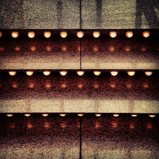Closeup of marble steps lit with strips of circular lights.