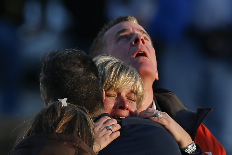 The families of victims grieve near Sandy Hook Elementary School, where a gunman opened fire on school children and staff in Newtown, Connecticut. A heavily armed gunman opened fire on school children and staff at a Connecticut elementary school on Friday, killing at least 26 people, including 20 children, in the latest in a series of shooting rampages that have tormented the United States this year. (Adrees Latif/Reuters)