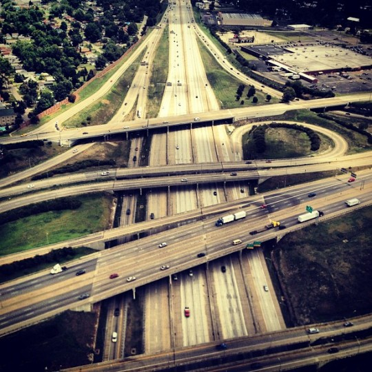Overhead shot exit ramps/entry lanes and four overpasses at a freeway function.